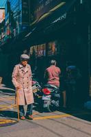 homme en manteau brun debout près de moto noir et rouge