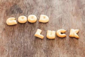 Biscuits alphabet bonne chance sur une table en bois