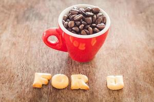 pour u biscuits alphabet avec une tasse de café rouge