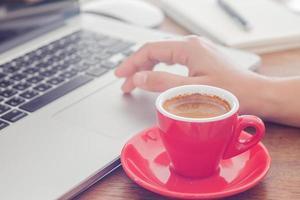 tasse à café rouge et une personne sur un ordinateur portable