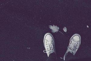 Personne portant des baskets blanches sur un fond sombre photo
