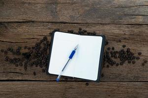 bureau en bois avec cahier et grains de café