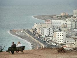 Rhodes, Grèce 2019-touristes s'asseoir sur un banc face à une mer calme en Grèce photo
