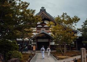 Deux gesha marchant sur une passerelle en béton à côté des arbres photo