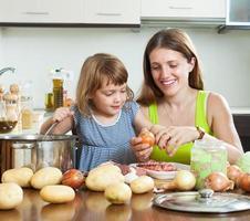 heureuse mère avec enfant cuisine soupe photo