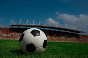 ballon de football sur herbe avec fond de stade photo