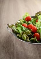 Salade fraîche avec légumes et verts sur table en bois photo
