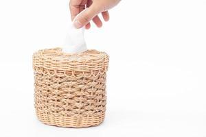 main avec une boîte de mouchoirs tissés