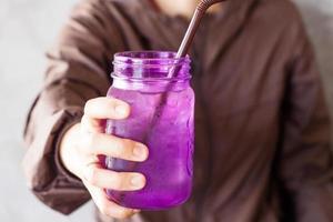 personne tenant un verre violet