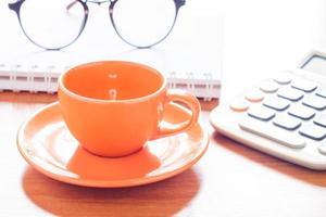 tasse à café orange avec une calculatrice et des verres