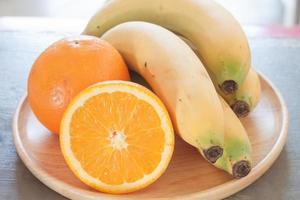assiette en bois avec des oranges et des bananes dessus