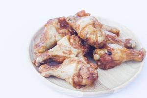 Pilons de poulet sur une plaque de bois photo