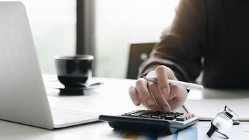 femme affaires, utilisation, calculatrice, et, ordinateur portable, bureau, bureau