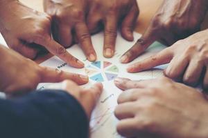 Groupe de partenaires commerciaux pointant vers la feuille graphique photo