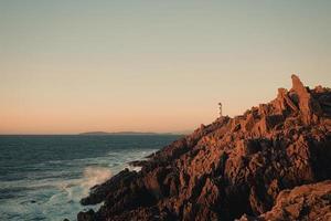 phare blanc sur d'énormes rochers risqués