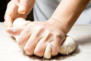 mains pétrissant une pâte.