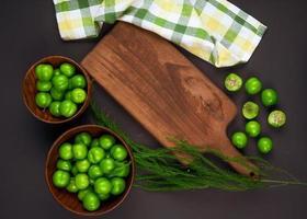 Vue de dessus des prunes aigres dans des bols en bois avec une planche à découper en bois