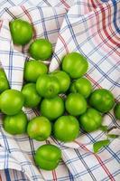 prunes vertes sur tissu à carreaux