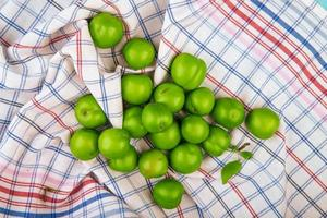 prunes vertes aigres éparpillées sur un tissu à carreaux
