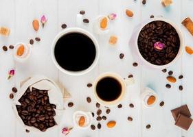 Vue de dessus des tasses à café et des haricots sur fond blanc photo