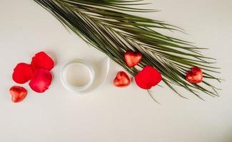 Vue de dessus des pétales de rose rouges et des bonbons au chocolat en forme de coeur avec une feuille de palmier