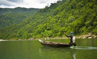 Les hommes ramant un bateau près de la colline verte pendant la journée