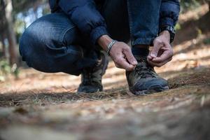 Homme jeune randonneur attache ses lacets de chaussures lors de la randonnée dans la forêt