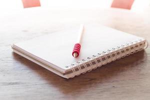 cahier et un crayon rouge au soleil