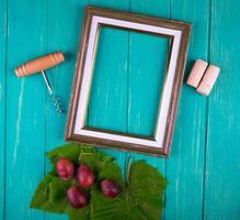 Vue de dessus d'un cadre photo vide avec un ouvre-bouteille, un bouchon de vin et des raisins