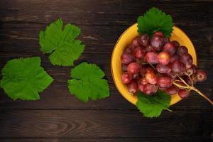vue de dessus d'un bol de raisins et de feuilles