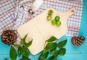 Vue de dessus d'une planche de bois avec des prunes et des pommes de pin sur tissu