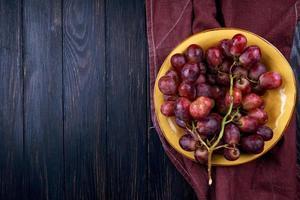 Vue de dessus d'un bol de raisins sur un fond en bois foncé