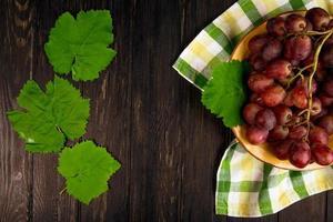 Vue de dessus d'un bol de raisins rouges et de feuilles sur tissu photo