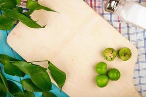 Vue de dessus d'une planche à découper en bois avec des prunes aigres