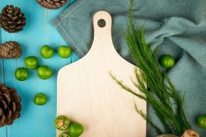 Vue de dessus d'une planche de bois avec des prunes vertes et des pommes de pin photo
