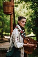 Fille ukrainienne dans une robe traditionnelle avec un seau dans ses bras photo