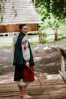 belle fille dans une robe brodée traditionnelle marche pieds nus photo