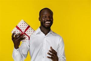 homme heureux souriant à la caméra et tenant un cadeau photo