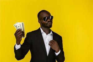 homme en costume et lunettes de soleil tenant de l & # 39; argent