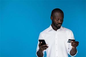 homme utilisant une carte de crédit pour acheter quelque chose en ligne