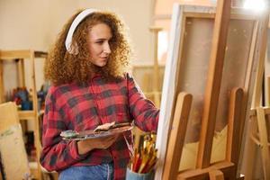 l'artiste écoute de la musique via des écouteurs et des peintures photo