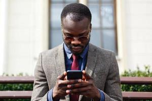 homme portant des lunettes de soleil travaille sur son téléphone photo