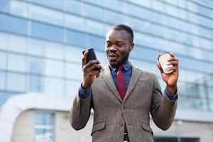 homme avec un café lisant sur son téléphone photo