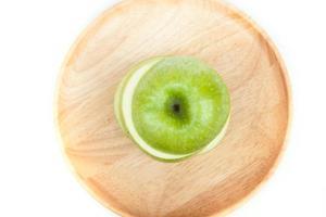 vue de dessus d'une pomme verte sur une assiette en bois