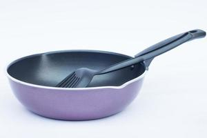 Poêle à frire violette avec une spatule sur fond blanc