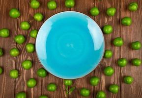 vue de dessus d'une assiette bleue et prunes vertes aigres