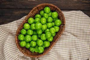 Vue de dessus des prunes aigres dans un panier en osier sur tissu vérifié sur fond de bois foncé