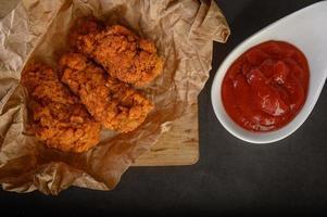 Poulet frit croustillant sur une planche à découper avec sauce tomate, vue du dessus photo