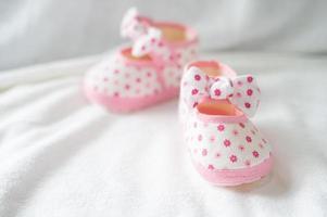 chaussures nouveau-né sur une literie blanche photo