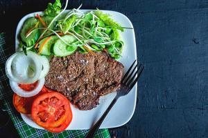 Steak aux légumes sur une assiette blanche photo